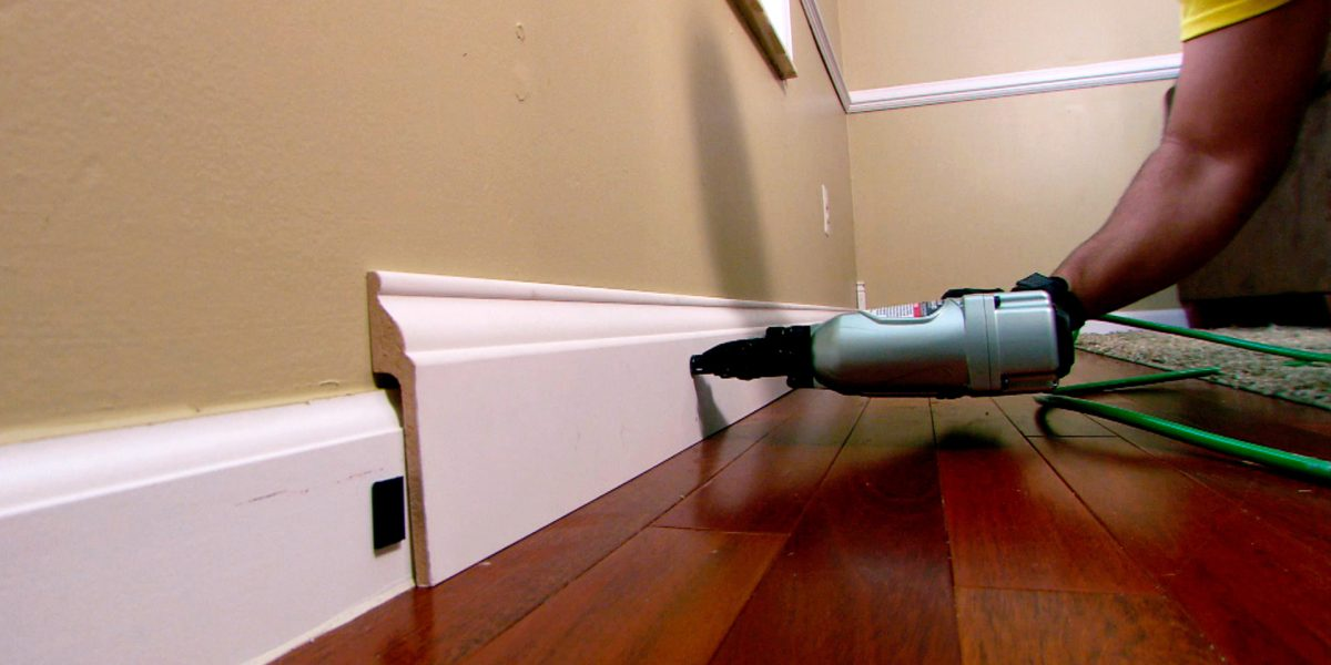 A close up of a nail gun as it is used to help install a Rapid Fit baseboard on top of the existing.